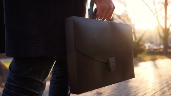 Business Man with Diplomat in His Hands Walks After Work in Sunset Light City