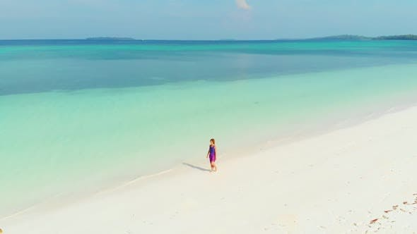 Cover Image for Aerial Slow motion: woman walking on white sand beach turquoise water tropical coastline