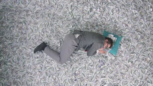 a Businessman Man Sleeps Against the Background of Banknotes on a Pillow Vertical Video Screen