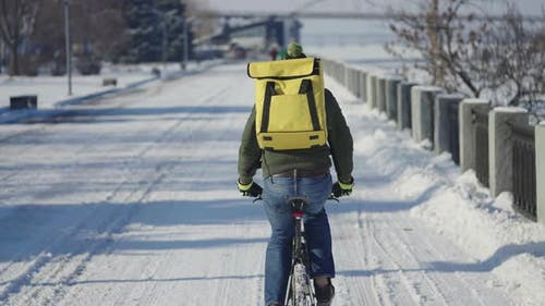 Back View of Man with Large Yellow Thermo Bag on His Back Rides Bicycle Along Snowy Street and