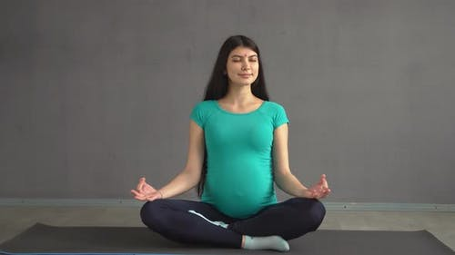Pregnant Ethnic Girl Engaged in Yoga Sitting in a Lotus Pose. Indian Woman with Hindi