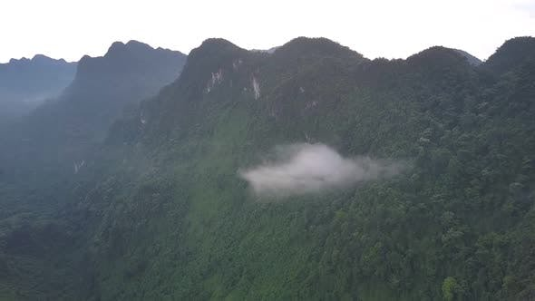 Thumbnail for Small Cloud Hangs Among Forest of High Mountain Range
