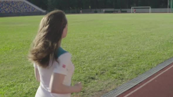 Cover Image for Athletic Young Girl Runs in the Stadium. Slow Motion