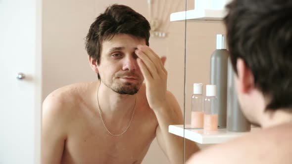 Thumbnail for Tired Man Who Has Just Woken Up Looking at His Reflection in the Mirror and Straightens His Hair