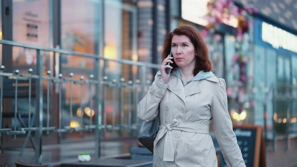 Business woman talking on phone on the go