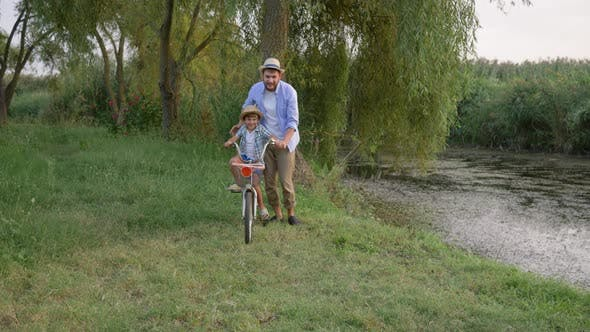 Thumbnail for Father and Son Learning To Ride Bicycle Having Fun Together on Background Outdoor Nature and Small