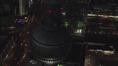 AERIAL: Close Up of Berlin Germany TV Tower Alexanderplatz at Night with City Lights Traffic