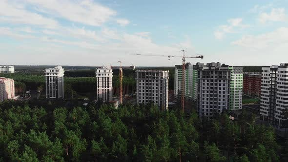 Construction of modern fashionable residential complex surrounded by pine trees in green forest