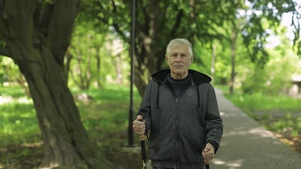 Thumbnail for Active Senior Old Man Training Nordic Walking with Ski Trekking Poles in Park