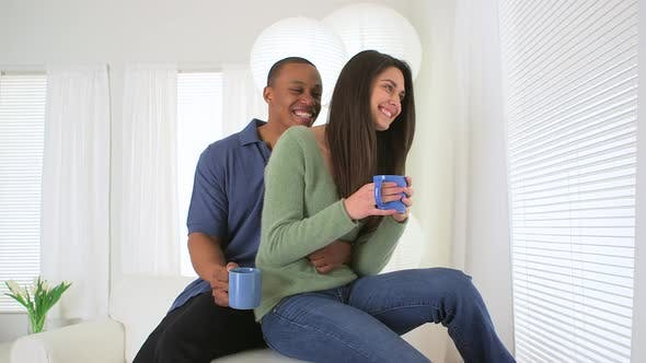 African American and Caucasian couple drinking coffee together