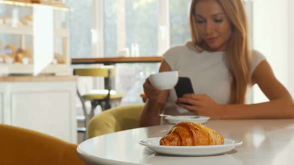Thumbnail for Selective Focus on Tasty Croissant, Woman Using Smart Phone at the Coffee Shop