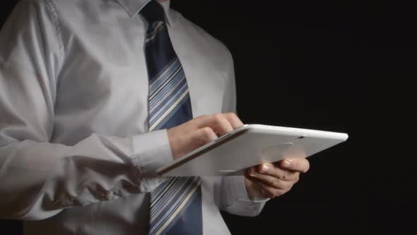 Thumbnail for Man in a white shirt and a tie holds a white tablet PC at hands