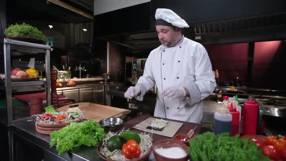 Thumbnail for Sushi Chef Making Sushi Rolls With Cucumber, Restaurant Kitchen