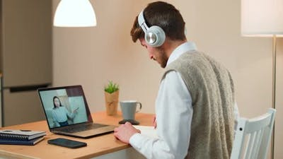 Male Student Sits at a Desk at Home and Study Online Using a Laptop Student Learns in a Remote