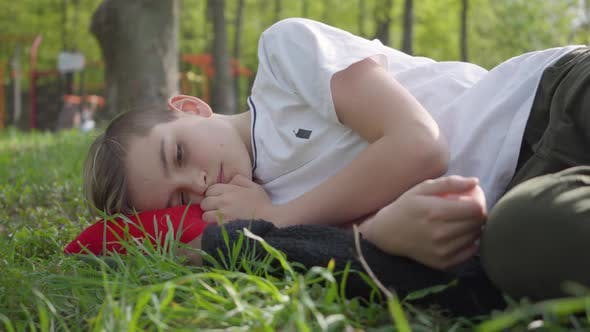 Thumbnail for Portrait of a Cute Boy Lying on Green Grass in Spring Park. Outdoor Recreation