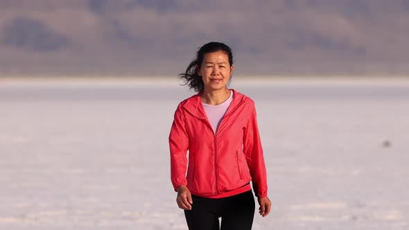Thumbnail for Asian woman jogging across the Bonneville Salt Flats flats