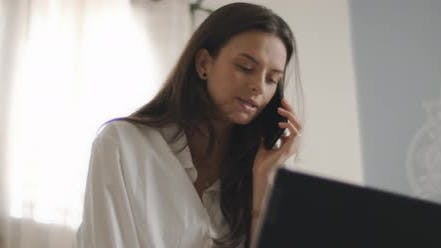 Thumbnail for Close up of a woman in white shirt talking to someone on the phone