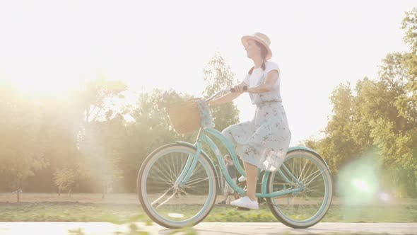 Thumbnail for Happy cheerful woman is riding vintage bike and enjoying outdoor leisure activity in summer.