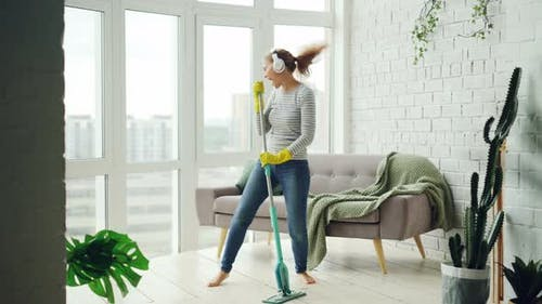 Happy Housewife Is Dancing and Singing During Housecleaning, She Is Listening To Music in Headphones