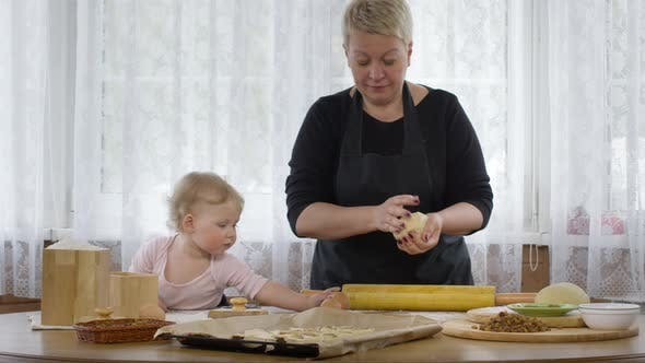 Thumbnail for Little Cute Baby Granddaughter Helps Granny Cook Dough for Pastry. Cozy Interior