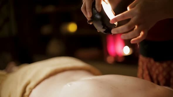 Thumbnail for Massage therapist pouring warm oil on clients body making relaxing massage