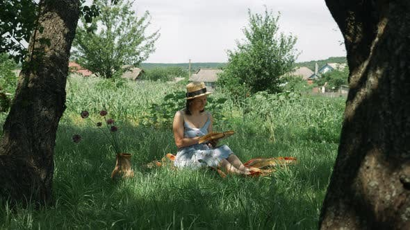 Thumbnail for Attractive caucasian woman sitting on grass at green garden and reading book at summer sunny day.