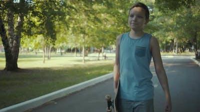 Skateboarder Walks in a Park with a Skateboard in Hands.