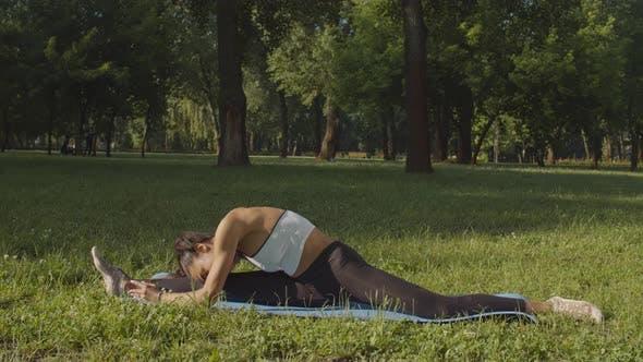 Thumbnail for Flexible Female Doing Splits on Yoga Mat Outdoor
