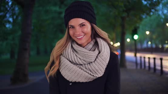 Smiling woman in cozy hat and scarf outside at night