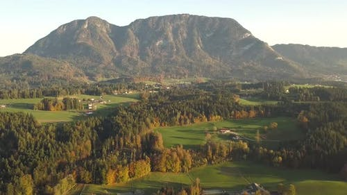 Aerial view of green meadows with villages and forest in austrian Alps mountains.