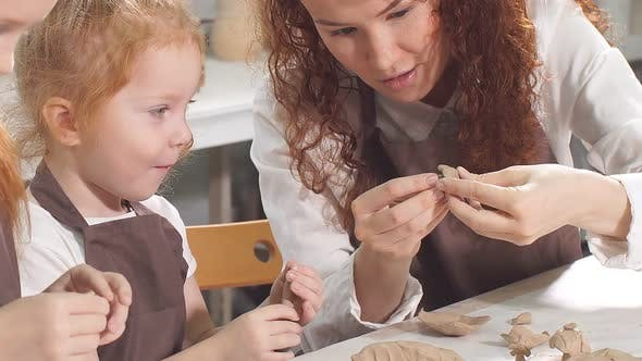 Teacher Helps the Kid To Cut Out a Clay Figurine with Spatula or Knife, Shows and Explanes