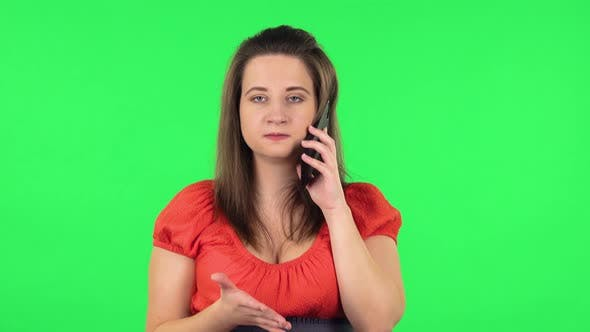 Thumbnail for Portrait of Cute Girl Angrily Speaking on the Phone, Proving Something . Green Screen