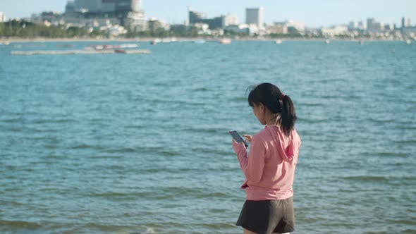 Asian in sportswear using a smartphone typing message chatting with friends after running.