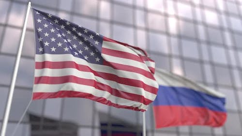 Flags of the USA and Russia in Front of a Skyscraper