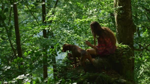 Thumbnail for Girl and dog in a forest