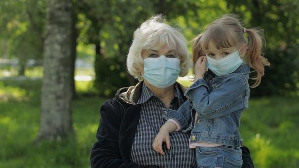 Großmutter mit Enkelin nimmt Masken nach Coronavirus Quarantäne Ende