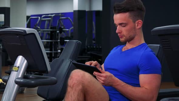 Thumbnail for A Young Fit Man Trains on a Recumbent Bike in a Gym and Works on a Tablet - Closeup
