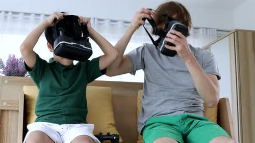 Funny father and son enjoying video games wearing VR headsets at home.