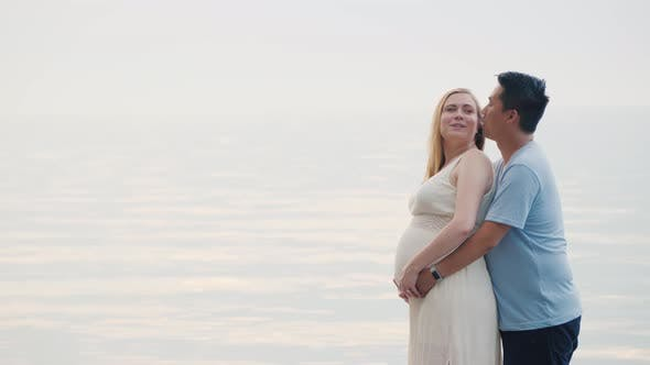 A Young Asian Man Hugs His Pregnant Wife on a Sunset Background Over the Sea