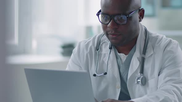 African American Physician Working On Laptop