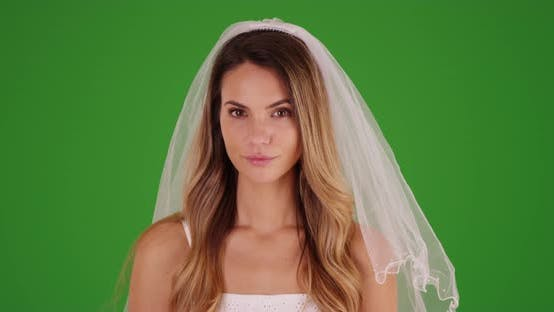 Thumbnail for Beautiful female millennial standing in a wedding dress and veil on green screen