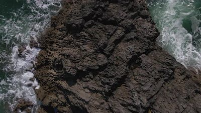 Aerial Shot Zooming Out From A Rock In The Sea
