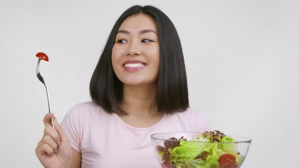 Happy Asian Woman Dancing And Eating Salad Over White Background