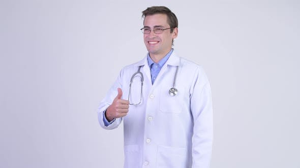Cover Image for Young Happy Handsome Man Doctor Giving Thumbs Up