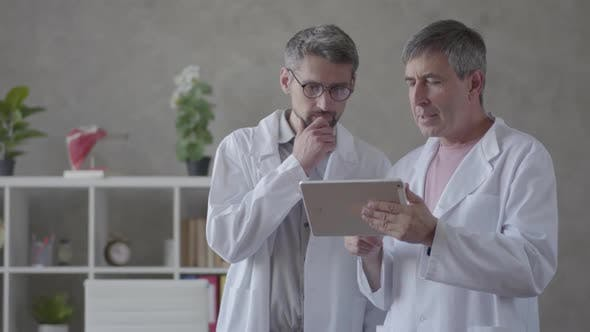 Two Male Doctors Checking Information on the Tablet, Discussing. Concept of Medicine, Technology