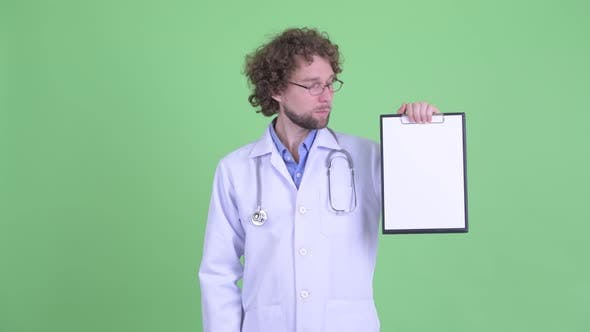 Cover Image for Happy Young Bearded Man Doctor Presenting with Clipboard and Giving Thumbs Up
