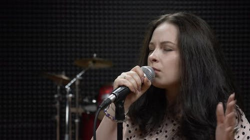 Attractive woman is singing romantic ballads into microphone in professional modern vocal studio.