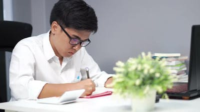young man studying and writing on notebook with laptop computer