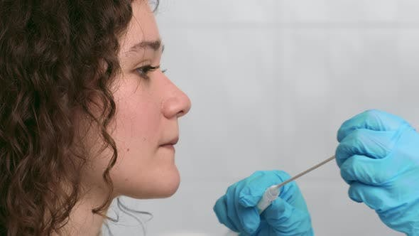 Laboratory Worker Taking PCR Throat Sample for Covid19 Test From Young Female Patient