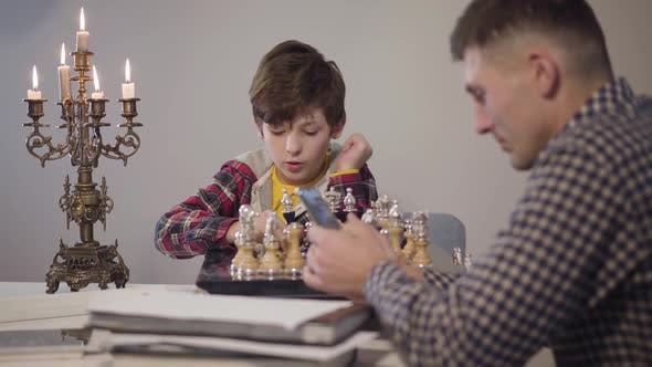Thumbnail for Portrait of Cute Smart Caucasian Boy Placing Chess on Board and Talking To Father Sitting at the
